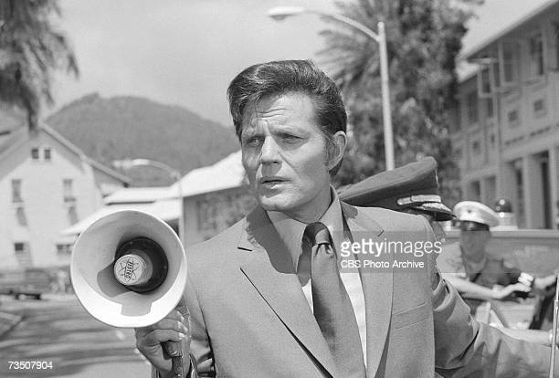 American actor Jack Lord born John Joseph Patrick Ryan speaks into a bullhorn in character as Steve McGarrett during the episode 'Death is a Company...