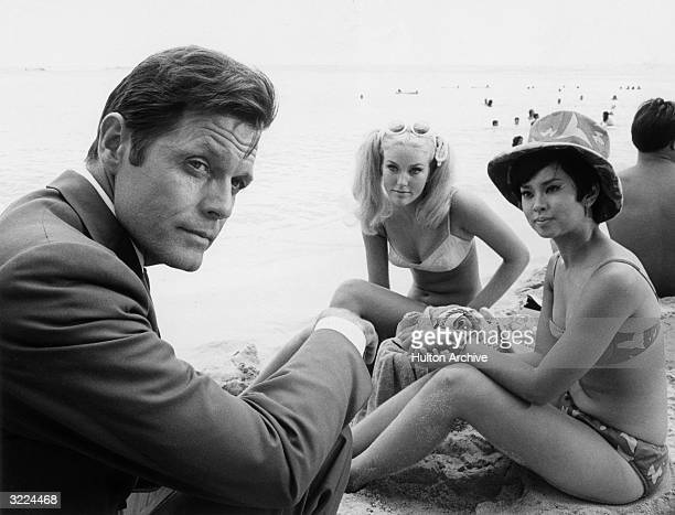 American actor Jack Lord sitting on a beach next to two women in bikinis in a still from the television show 'Hawaii FiveO'