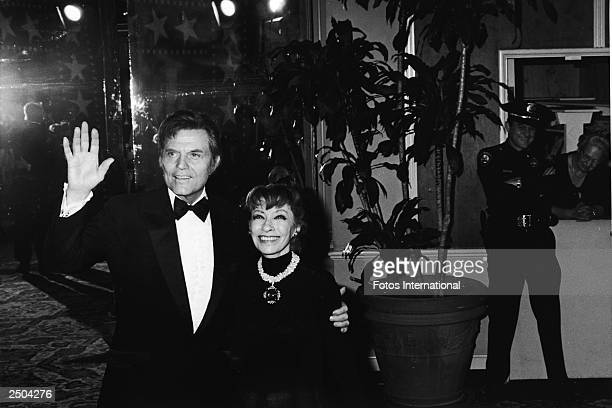 American actor Jack Lord waves as he and his wife Marie attend the American Film Institute Salute to movie director Frank Capra held at the Beverly...