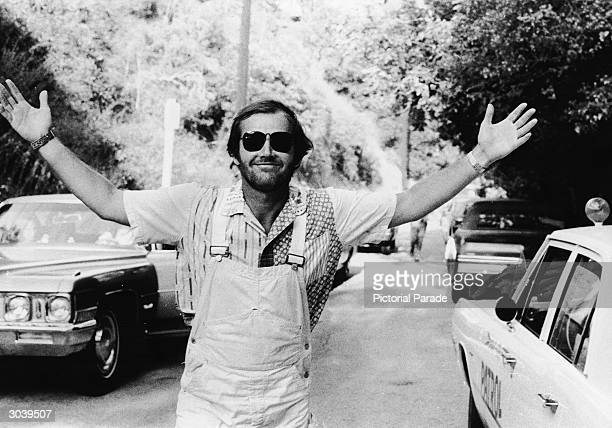 American actor Jack Nicholson smiles with his arms outstretched wearing overalls and sunglasses while attending the Motion Picture Relief Fund...