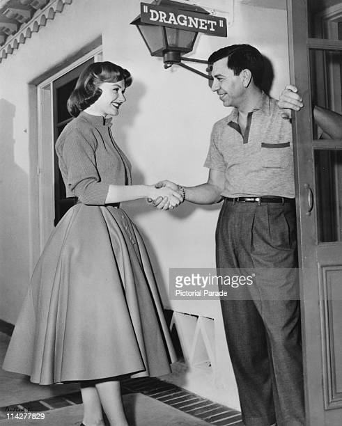 American actor Jack Webb welcomes actress Ann Robinson onto the set of the film 'Dragnet' USA 1954 Robinson plays Officer Grace Downey in the film...