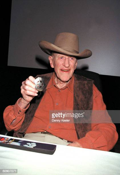 American actor James Arness wears a cowboy hat and shows his sheriff's badge from the TV series 'Gunsmoke' during a book signing for his 'James...