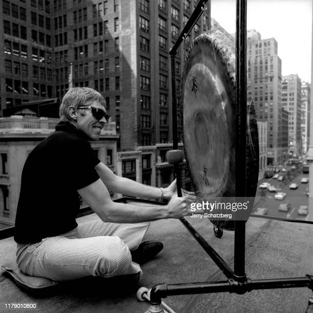 American actor James Coburn bangs a large metal gong as he sits on the roof of a Park Avenue building New York New York June 27 1967