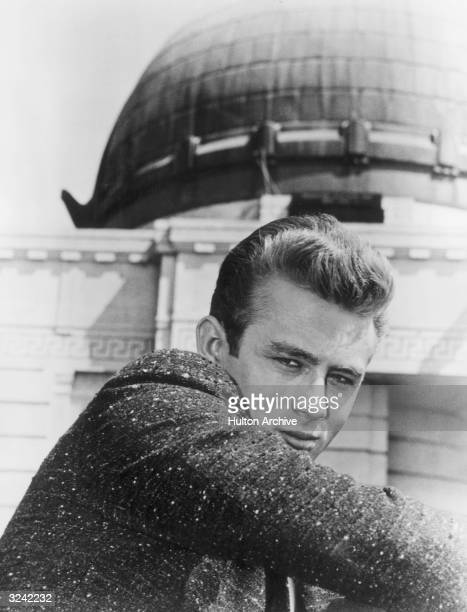 American actor James Dean as Jim Stark looks over his shoulder while sitting in front of the Griffith Observatory in a promotional portrait for...