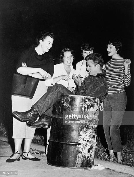 American actor James Dean smokes a cigarette and signs autographs for a pack of enthralled female fans while he sits in a trashcan 1950s