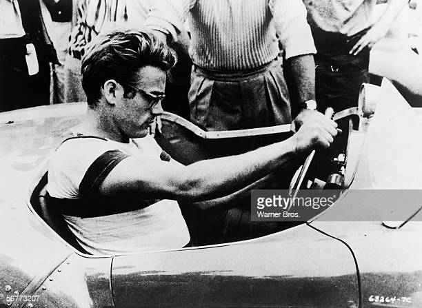 American actor James Dean sits behind the wheel of a sportscar in a still from the documentary movie 'The James Dean Story' directed by Robert Altman...