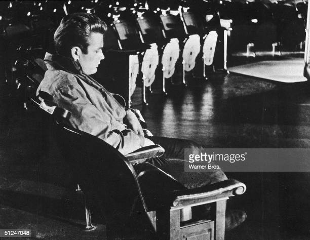1955 American actor James Dean sits in empty theater in a still from director Nicholas Ray's film 'Rebel Without a Cause'