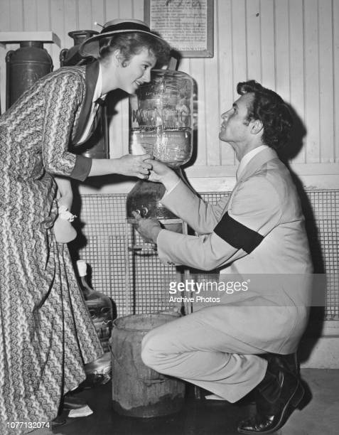 American actor James Mitchell helps costar Amanda Blake to a cup of Magnetic Spring Water on the set of the film 'Stars In My Crown' 1950