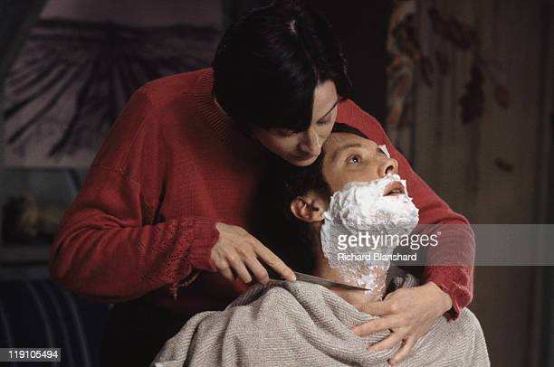 American actor James Spader stars with French actress Anne Brochet in the film 'Driftwood' 1997 In this scene she gives him a wet shave with a knife