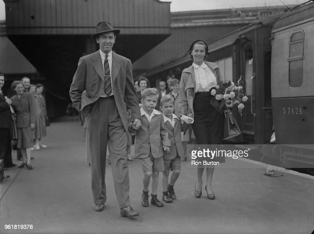 American actor James Stewart arrives at Waterloo Station in London with his wife actress and model Gloria Hatrick McLean and her sons Ronald and...