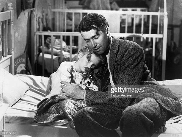 American actor James Stewart as George Bailey hugs actor Karolyn Grimes who plays Zuzu his daughter in a still from director Frank Capra's Christmas...
