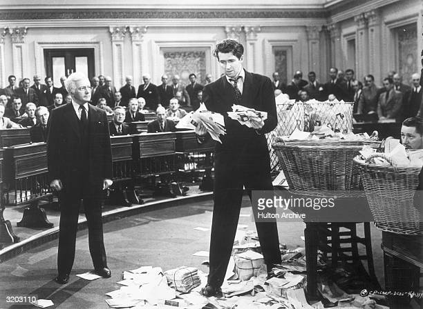 American actor James Stewart clutches a wad of letters as British actor Claude Rains looks on while standing on the floor of the US Senate in a still...
