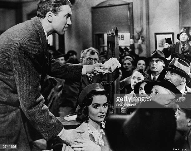 American actor James Stewart stands behind Donna Reed gesturing with a handful of money while speaking to a group of townspeople in a still from the...