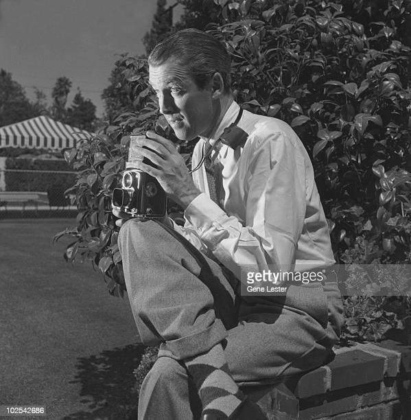 American actor James Stewart takes a photograph in his backyard California 1951