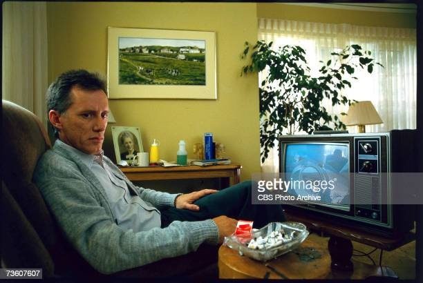 American actor James Woods sits in an armchair in front of a tv set in a scene from the television movie 'Promise' directed by Glenn Jordan Oregon...