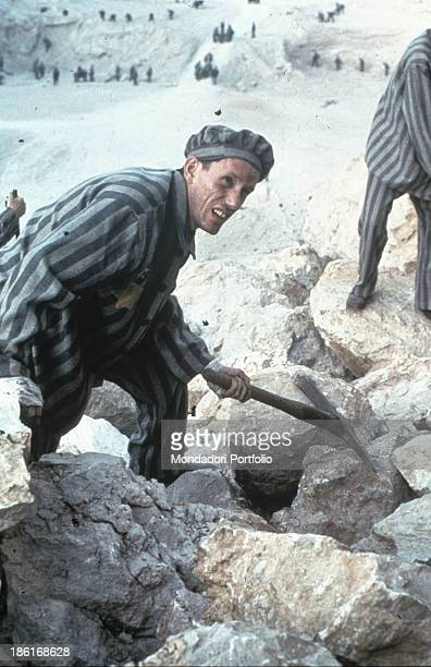 American actor James Woods wearing a deportee uniform and breaking stones with a pickaxe He acts in the TV miniseries Holocaust 1978
