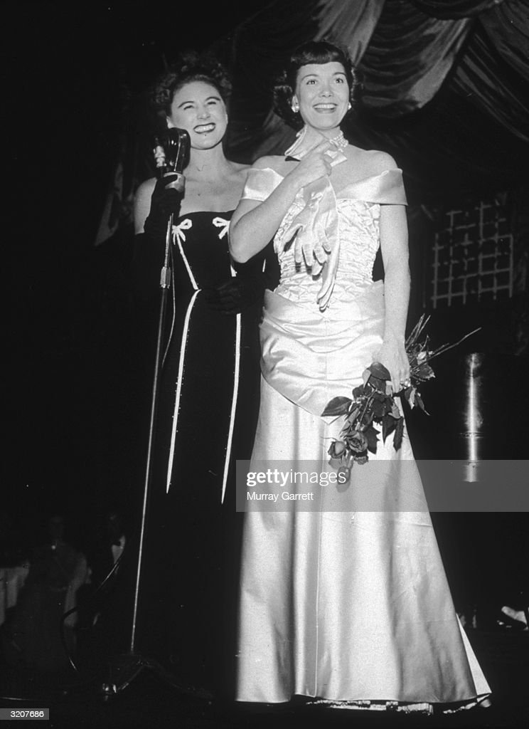 American actor Jane Wyman (C) and American cabaret singer Hildegarde stand together at the premiere of director Jean Negulesco's film, 'Johnny Belinda,' Los Angeles, California. Wyman, who starred in the film, holds a bouquet of roses, as Hildegarde stands beside her at a microphone.