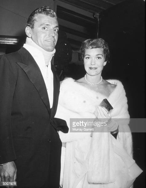 American actor Jane Wyman and Greg Bautzer wearing a neck brace stand together and smile while at the Damon Runyon Cancer Fund benefit party held at...