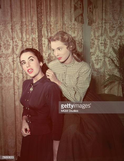 American actor Janet Leigh adjusts the bow in Britishborn actor Elizabeth Taylor's hair while on the set of 'Little Women' directed by Mervyn Leroy...