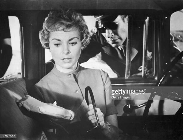 American actor Janet Leigh studies an envelope after removing it from her purse while a highway patrolman, played by actor Mort Mills , watches her...