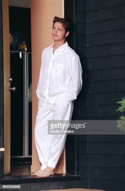American actor Jason Priestley barefoot and with white pants and shirt on leans against a wall on the set of the movie Life and Death on Long Island...