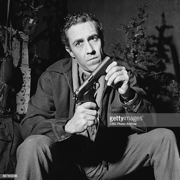 American actor Jason Robards caresses his gun in a still from the CBS television Playhouse 90 production of 'For Whom the Bell Tolls' directed by...