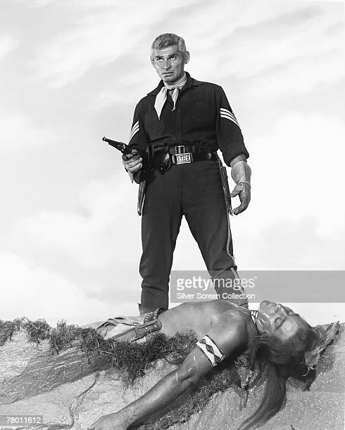 American actor Jeff Chandler stands over the dead body of a Native American in his role as First Sergeant Emmett Bell of the US Cavalry in the...