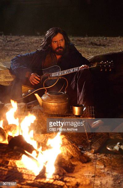 American actor Jeremy Davies as Charles Manson sits near a fire and plays guitar in a scene from the madefortelevision movie 'Helter Skelter'...