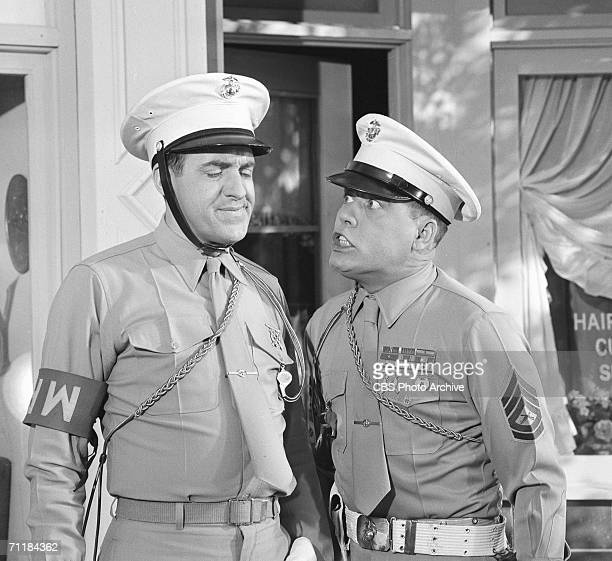 American actor Jim Nabors grimaces as fellow actor Frank Sutton trembles with anger in an episode of the television comedy series 'Gomer Pyle USMC'...