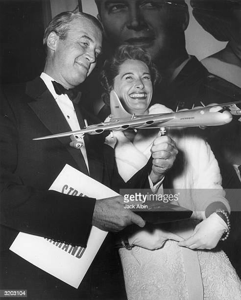 American actor Jimmy Stewart holding a scale model of a United States Air Force jet plane with his wife Gloria Stewart at the premiere of Anthony...