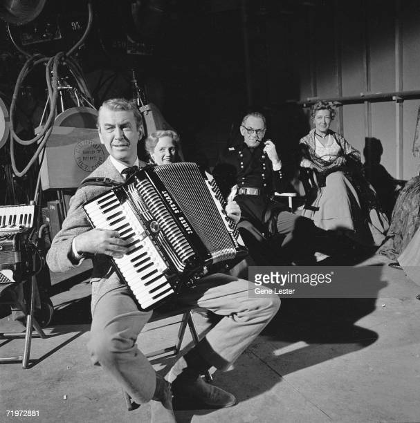 American actor Jimmy Stewart sits on a folding chair and plays his accordion behind the scenes of an unidentified film at the Colombia Picture Corp...