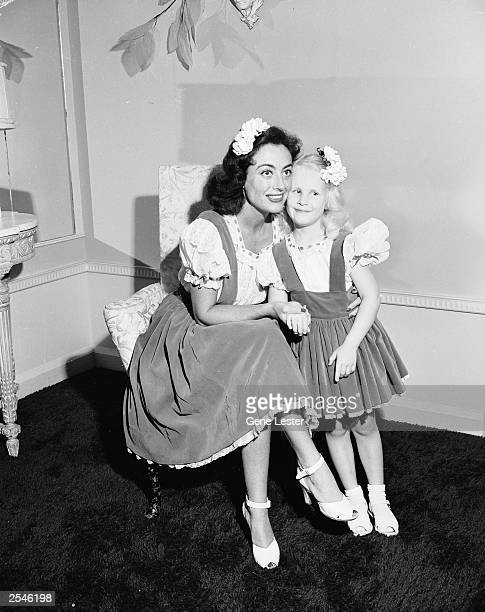 American actor Joan Crawford hugs her adopted daughter Christina wearing matching outfits June 1944
