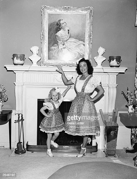 American actor Joan Crawford poses by a fireplace with her adopted daughter Christina June 1944