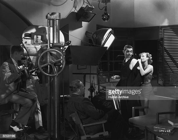 American actor Joan Crawford stands behind Clark Gable and removes his suit jacket before director Robert Z Leonard and a camera crew during shooting...