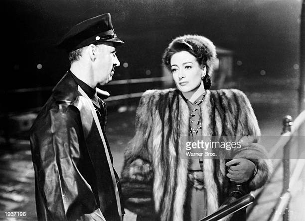 American actor Joan Crawford wears a fur coat as she stands next to a police officer in a still from director Michael Curtiz's film 'Mildred Pierce'...