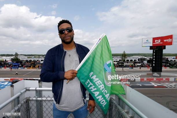 American actor Jocko Sims poses with the green flag prior to the start of the Monster Energy NASCAR Cup Series Pocono 400 at Pocono Raceway on June...