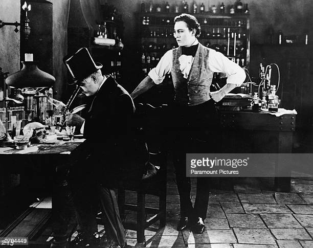 American actor John Barrymore stands in the middle of a laboratory as an unidentified actor in a top hat looks through a microscope in a still from...