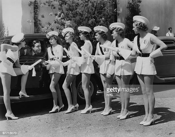 American actor John Boles with extras from his latest musical 'Redheads On Parade' directed by Norman Z McLeod at the Fox Film Corporation studios...