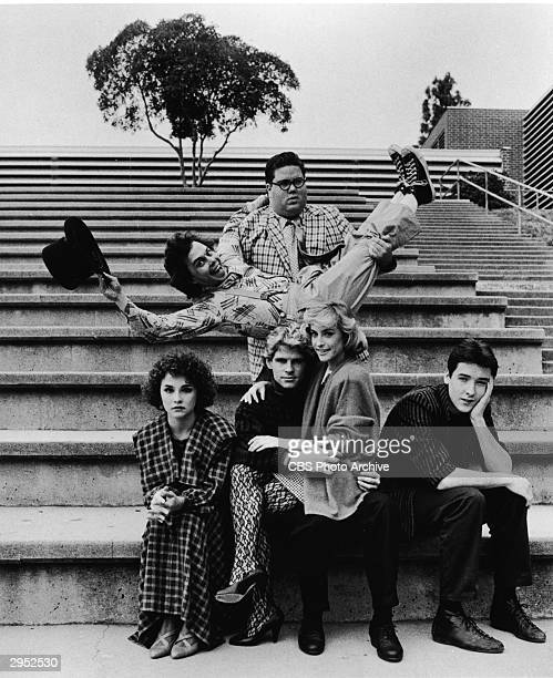 American actor John Cusack sits on a flight of stairs along with the rest of the cast in a publicity photograph from the film 'Better off Dead',...