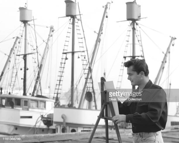 American actor John Derek painting boats in a harbour, circa 1950.