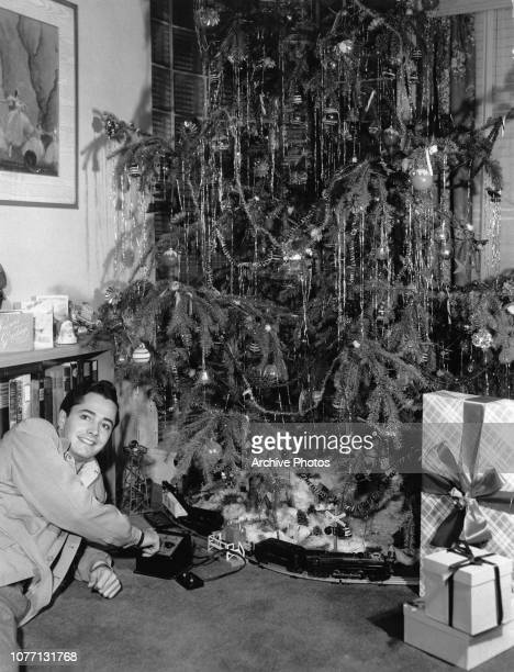 American actor John Derek plays with a train set under the Christmas tree circa 1955