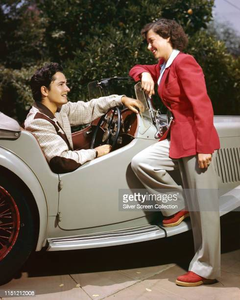 American actor John Derek with his wife, actress and ballet dancer Pati Behrs at the wheel of his MG TC Roadster, circa 1950.