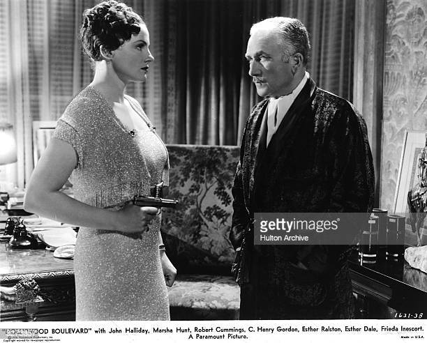 American actor John Halliday faces a gun held by Scottish actress Frieda Inescort in a scene from 'Hollywood Boulevard' directed by Robert Florey for...