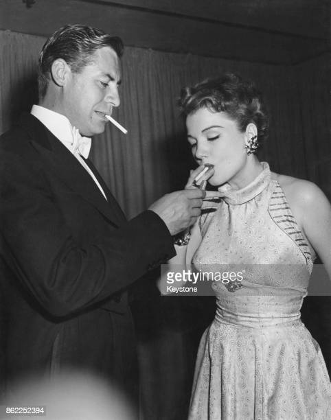 American actor John Hodiak lights a cigarette for his wife actress Anne Baxter USA 18th May 1950