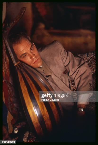 American actor John Malkovitch rests on cushions behind a lute guitar during the shooting of the movie Un The au Sahara or Il Te Nel Deserto...