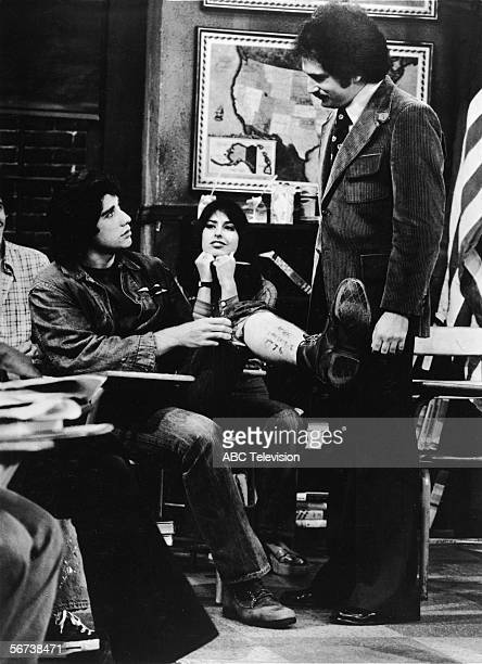American actor John Travolta looks up at colleague compatriot and professional poker player Gabe Kaplan as he he shows him what is written on his leg...