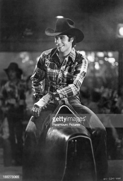 American actor John Travolta rides a bucking bronco machine in a scene from the film 'Urban Cowboy' 1980