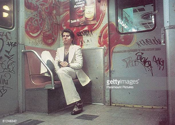 1977 American actor John Travolta sits on a bench inside a subway car painted with graffiti in a still from director John Badham's film 'Saturday...
