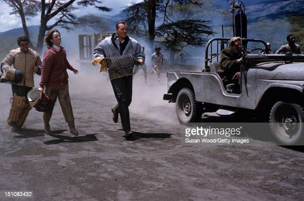 American actor John Wayne and Italian actress Elsa Martinelli carry protective gear as they run after a jeep during the filming of 'Hatari' Tanzania...