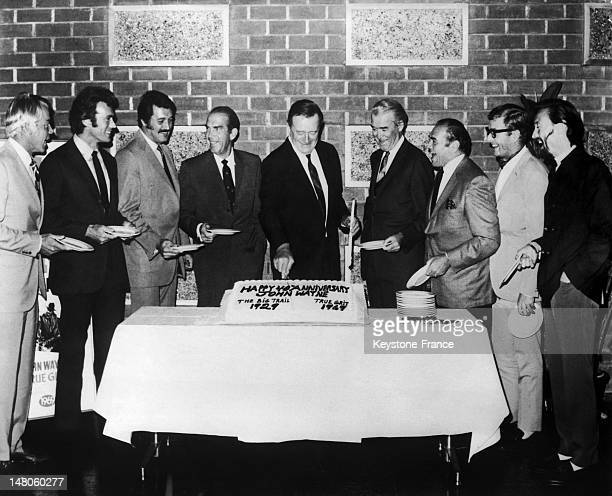 American actor John Wayne cutting the cake of its 40th anniversary of a movie career in Hollywood California in 1969 with from left to right Lee...
